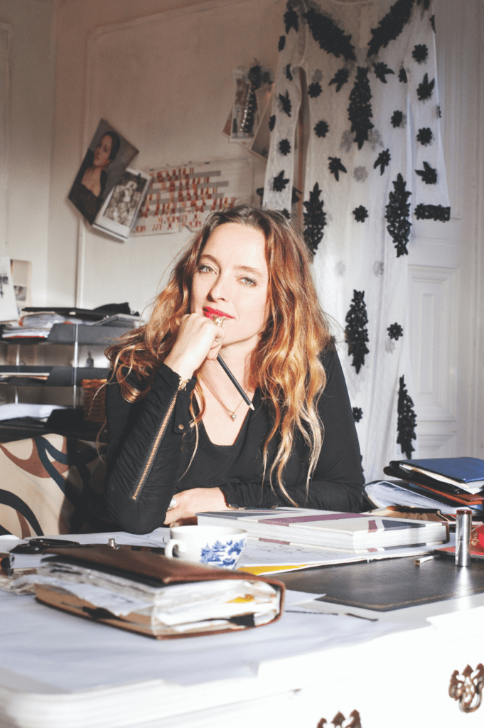Alice Temperley sitting at a desk in her office