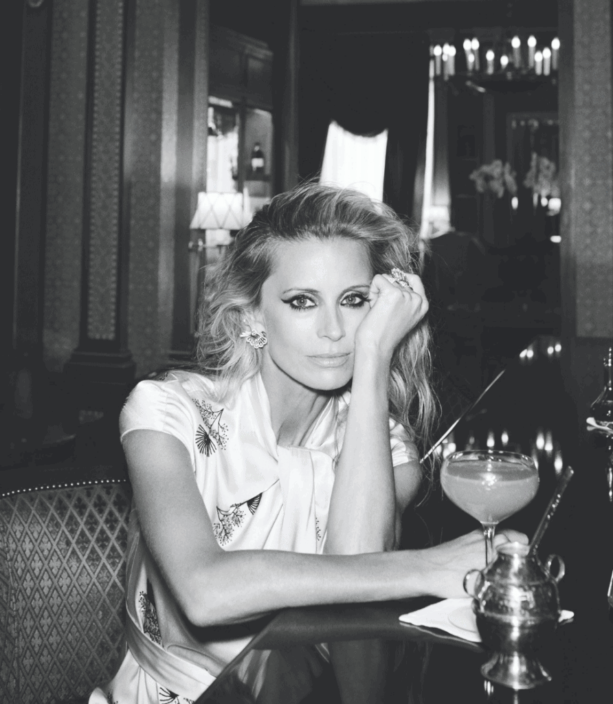 Laura Bailey sits at a bar with a cocktail