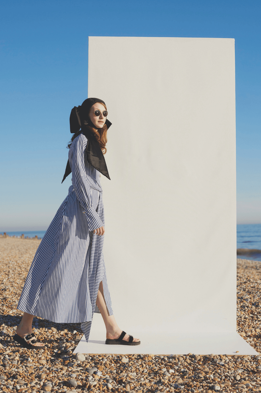 Model wears blue and white striped maxi dress by Mother of Pearl on a beach