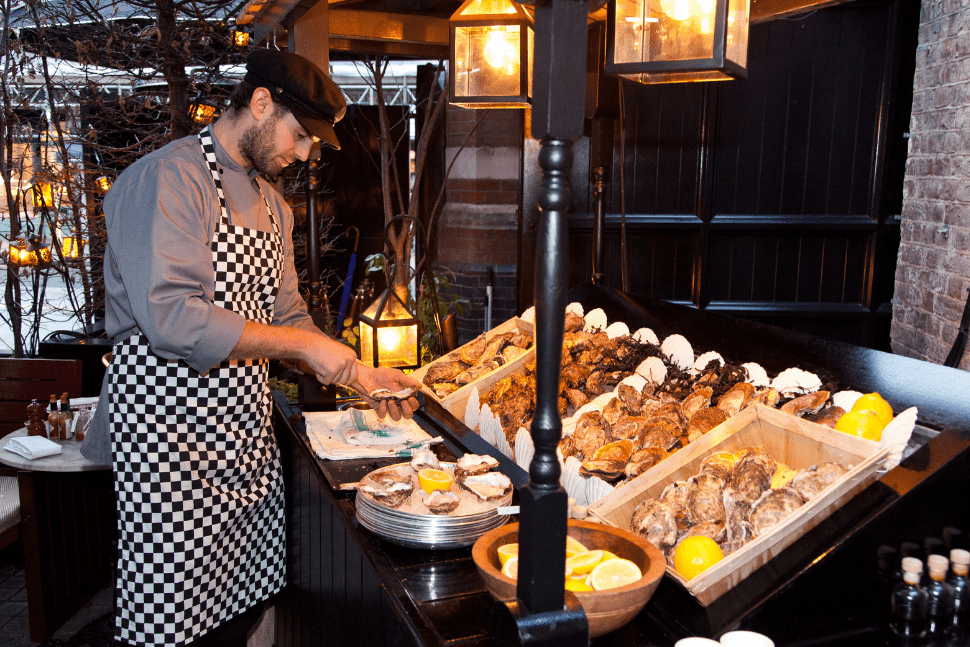 A chef prepares oysters from the seafood cart at Chiltern Firehouse in London