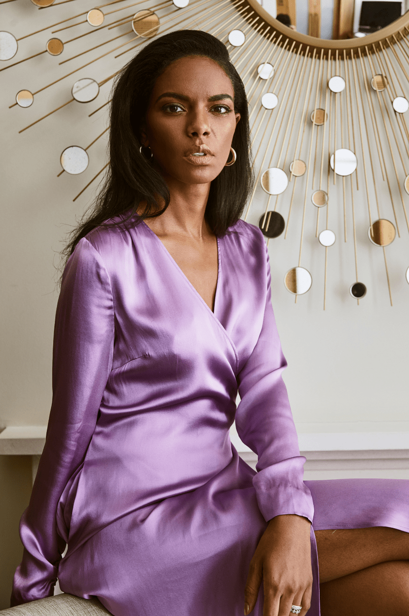 Noëlla Coursaris Musunka wears a purple satin wrap dress with gold hoops