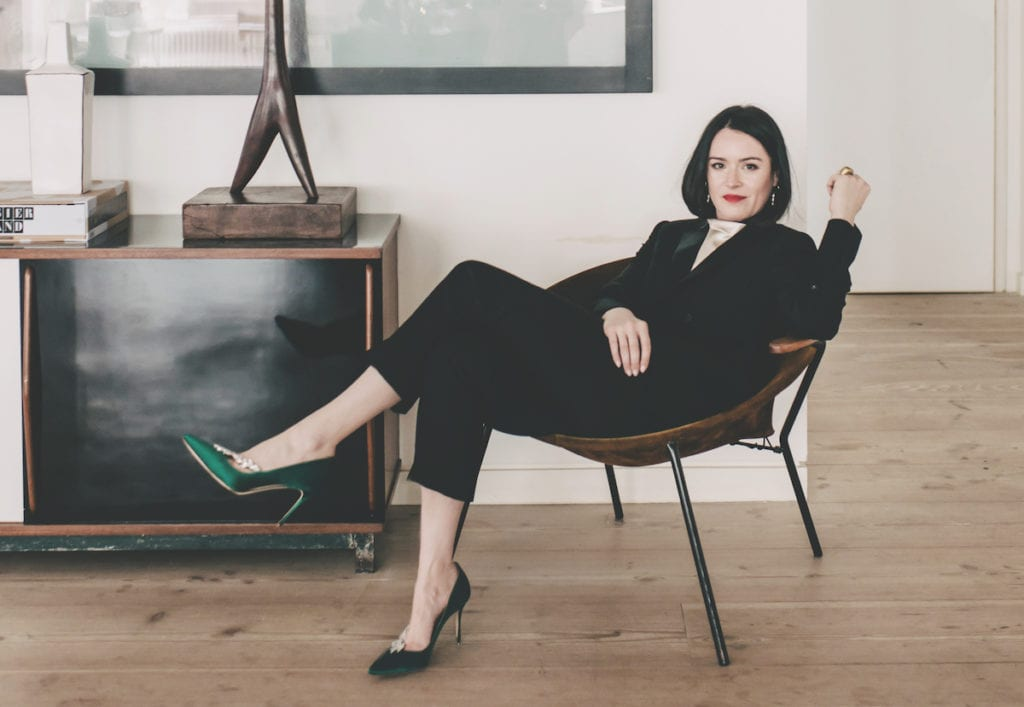 Portrait of Alex Eagle wearing a tuxedo suit and green satin shoes