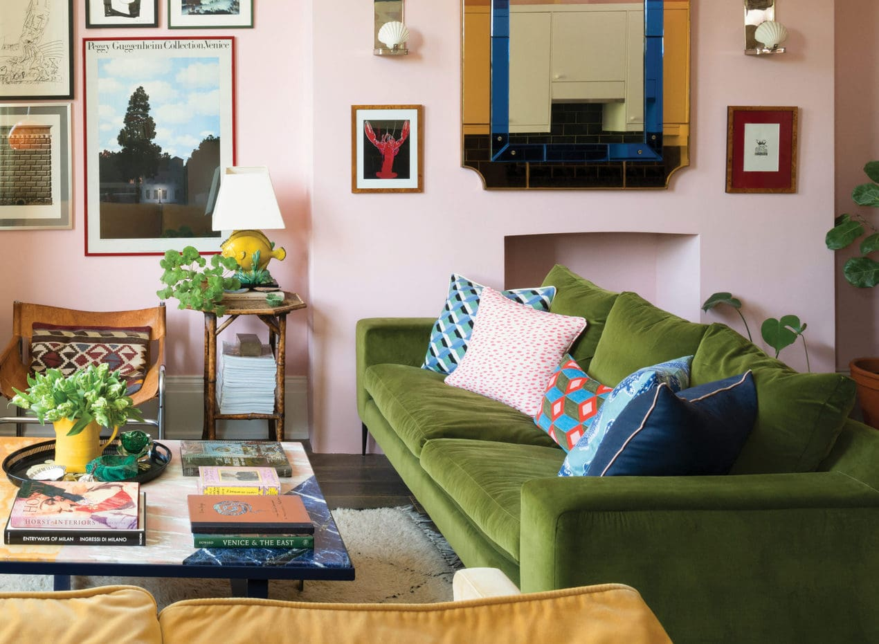 Luke Edward Hall's living room with pink walls and an olive green velvet sofa