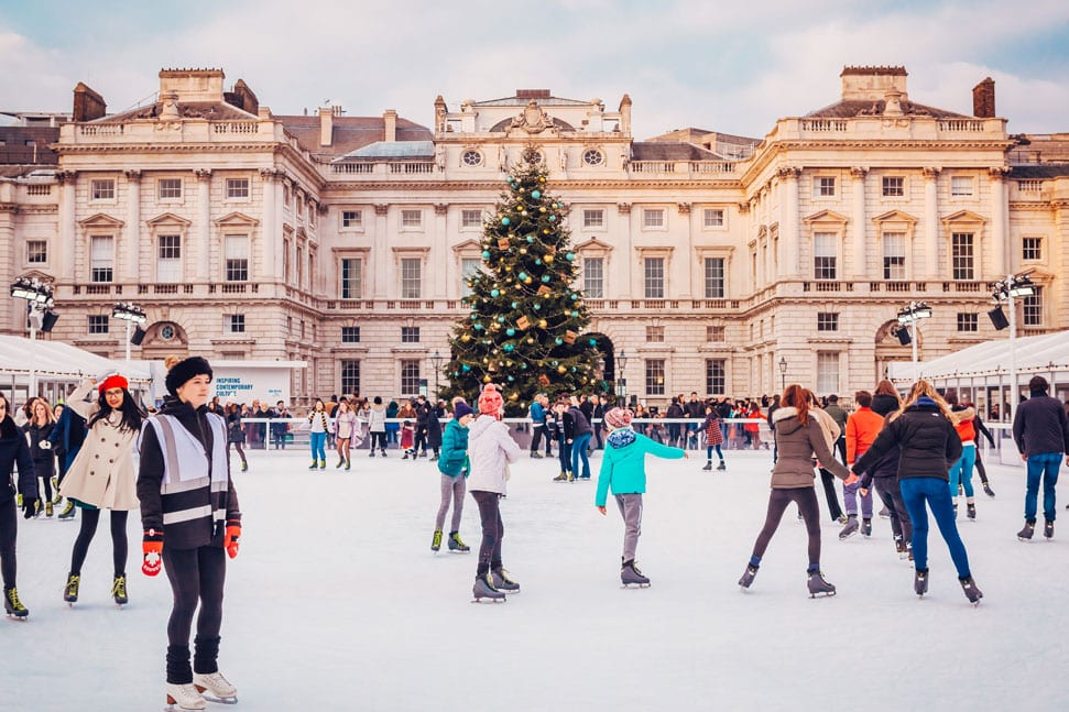 Ice skaters glide around the rink in front of the Christmas tree at Somerset House