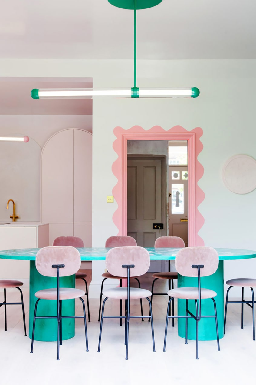 A 2LG kitchen design, with a green marble table, pink chairs and a pink-painted doorframe