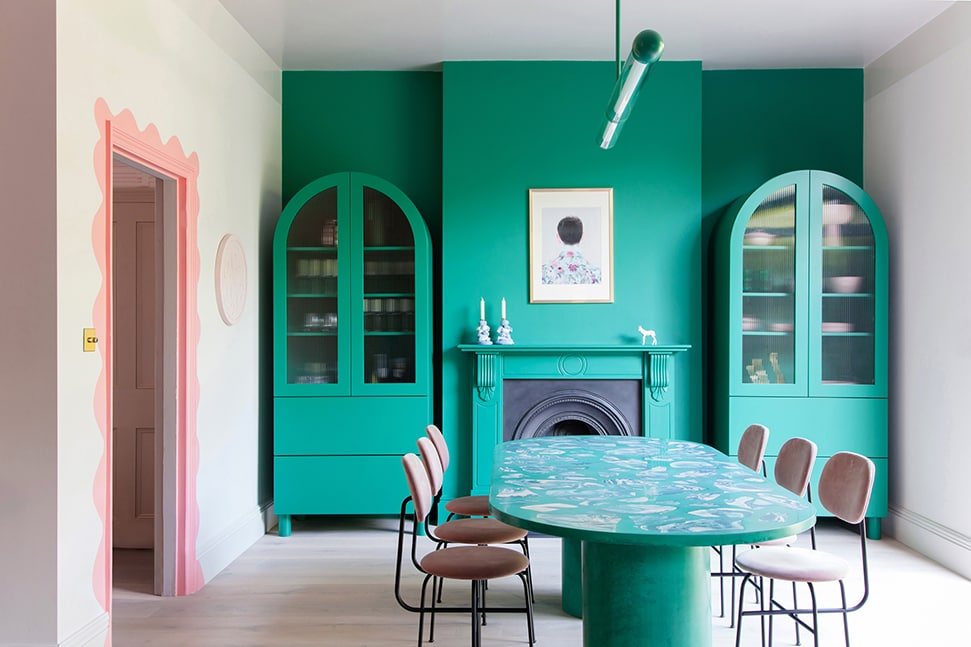 One of 2LG's kitchen designs, featuring a bright green wall and cabinets and a pink-painted doorframe