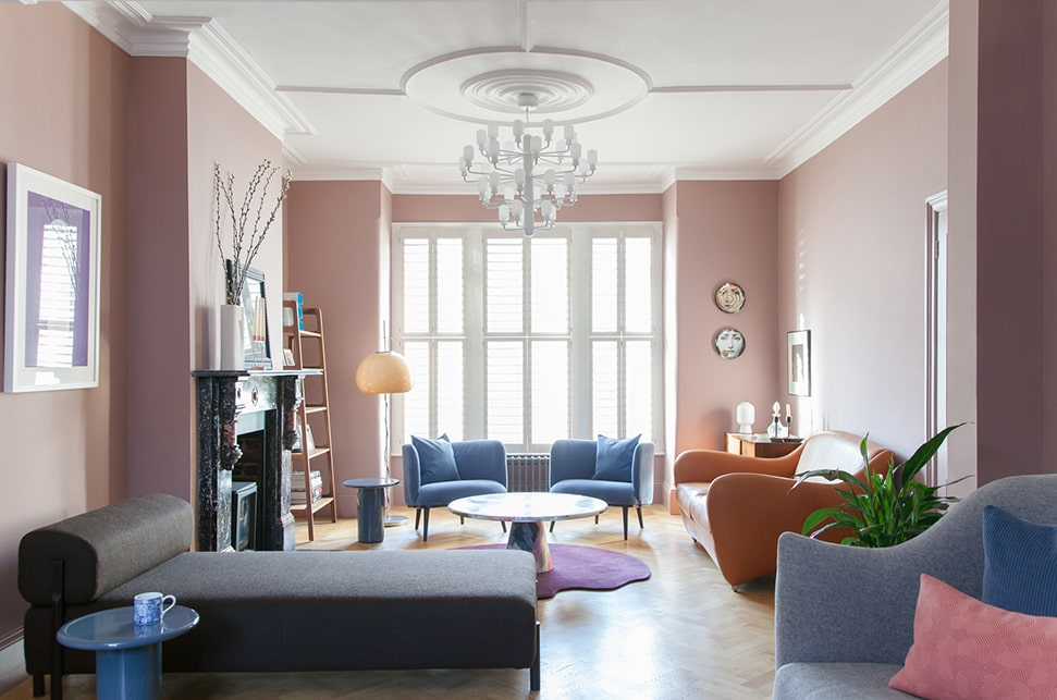 A pink sitting room with colourful furniture designed by 2LG