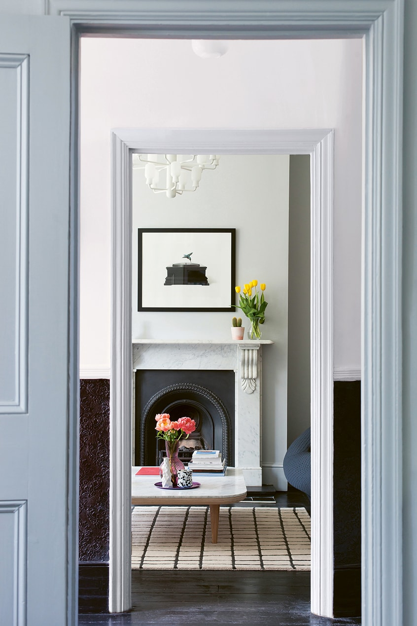 A view through the doorway of a house, featuring off-white walls, a key feature of 2LG's designs